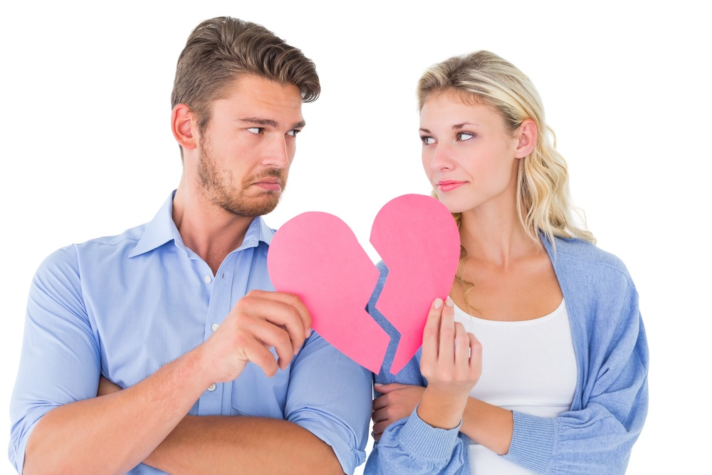 Couple holding two halves of broken heart on white background.jpeg