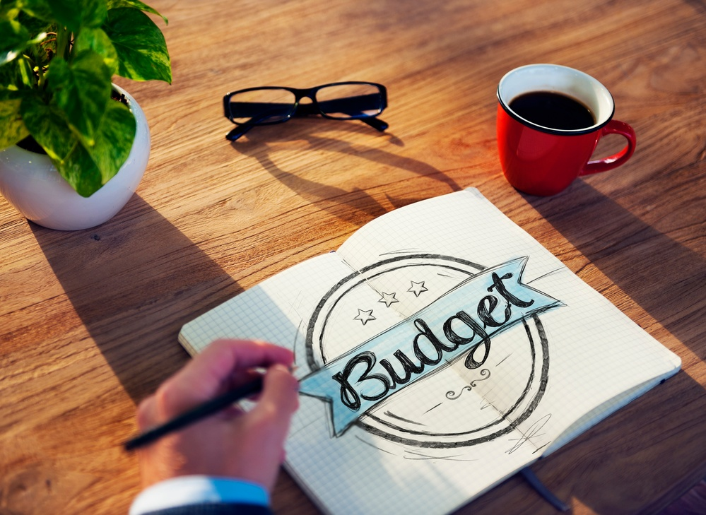 hand writing Budget on blue banner